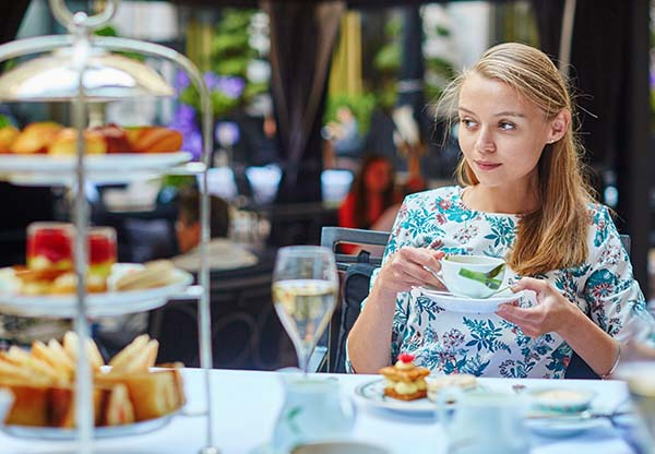 Young woman enjoying afternoon tea with selection of fancy cakes and sandwiches