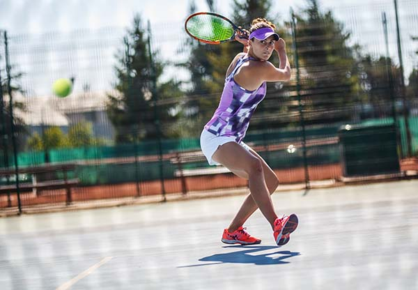 Tennis player hits the ball with Backhand slice.